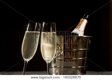 Champagne bottle in cooler and two champagne glasses on dark background