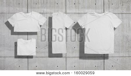 Unlabeled white shortsleeve cotton t-shirt folded in three different ways and lying flat on industrial concrete background