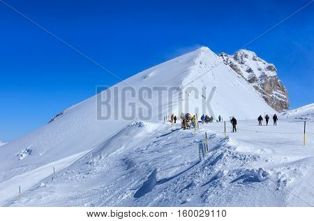 Mt. Titlis, Switzerland - 9 March, 2016: view on the top of the mountain on a windy day with show taken into the air by wind. Titlis is a mountain located on the border between the Swiss Cantons of Obwalden and Bern.