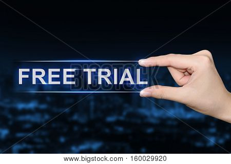 hand pushing free trial button on blurred blue background