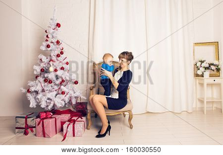 happy family mother and baby little son playing home on Christmas holidays. New Year's holidays. Toddler with mom in the festively decorated room with Christmas tree. Portrait of mother and baby boy.