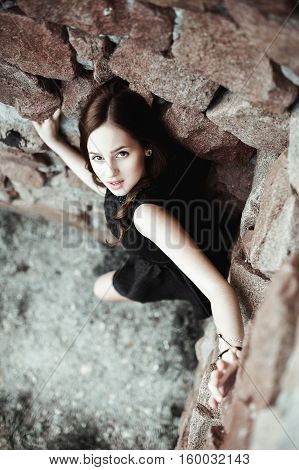 beautiful sad young woman on a stone wall background posing in a black dress very emotional