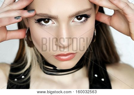 Punk rock style. Fashion woman model face with glamour makeup. Perfect skin black arrows on eyes and pale lips visage.
