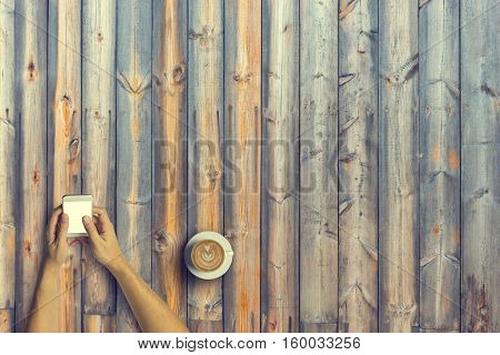 Top View Of Business People Using A Smartphone With A Cup Of Latte Coffee On Old Wooden Desk Backgro