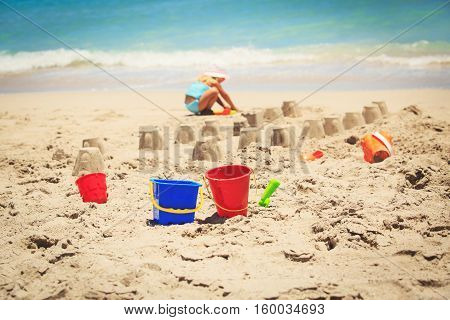 kids toys and little girl building sandcastle at tropical beach