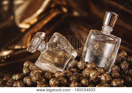 Bottle of woman perfume on gold background.