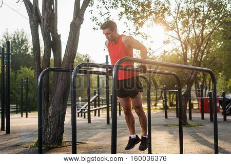 Fit man doing triceps dips on parallel bars at park exercising outdoors.