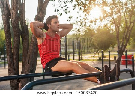 Fit man doing sit ups on parallel bars outdoor fitness station