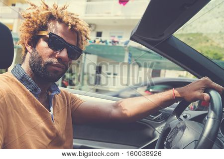 Young happy black man with dread locks wearing sunglasses sitting in the convertible car. Vintage filter applied.