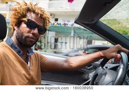 Young black man with dread locks wearing sunglasses sitting in the convertible car.