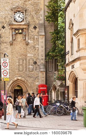 Oxford United Kingdom - June 20 2006: St Martin's Tower (Carfax Tower) with a clock that chimes the quarter hours on a pair of bells. K2 red telephone kiosk and post box beside St Martin's tower with bicycle parking. People of various ages walking shoppin