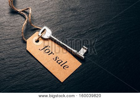 Old key with tag on black stone surface. Concept of real estate rent.