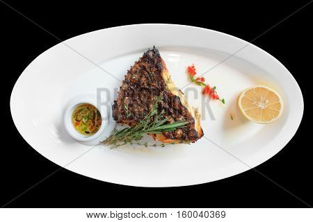 Grilled flounder on plate, isolated on black background