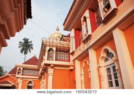 Orange Hindu temple architecture with a palm