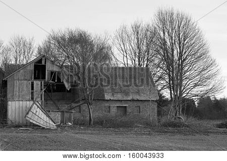 Black and white shot of an old farmhouse barn damaged in a storm