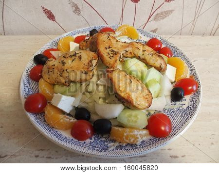 Dinner with pieces of chicken and raw colorful vegetables and fruits salad served on blue plate on table, DECEMBER 2016.