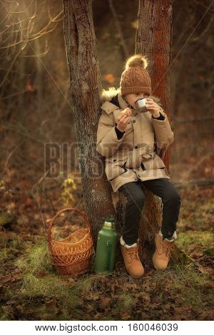 autumn forest boy sitting on a stump and drinking tea with pastries