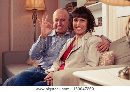 A mid shot of loving couple sitting in the room with modern interior. A man showing OK with his fingers, woman grinning from ear to ear