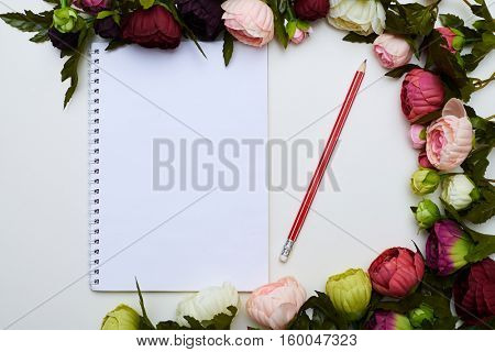A mid shot of white jotter and red pencil circled by beautiful peonies lying on the light field. Excellent image of stylish objects