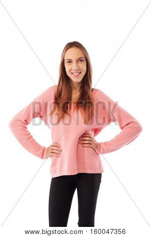 Mid shot of joyful and laughing softly teenage holding two hands on hips isolated over white background. Young long hair teenager in knitted sweater posing over white wall