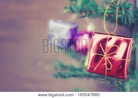 Christmas gift box ornaments hang on Christmas Tree have space soft focus.