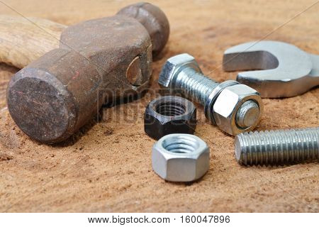 Macro shot of some tools with bolts and nuts on a wooden table top