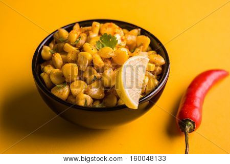 Steamed organic yellow sweet corn masala or corn chat prepared using butter, chat masala and lemon, favourite indian snack