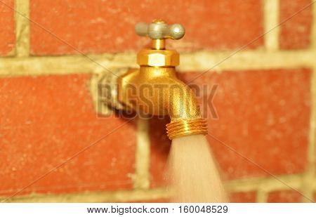Close up of a traditional water faucet open with water running