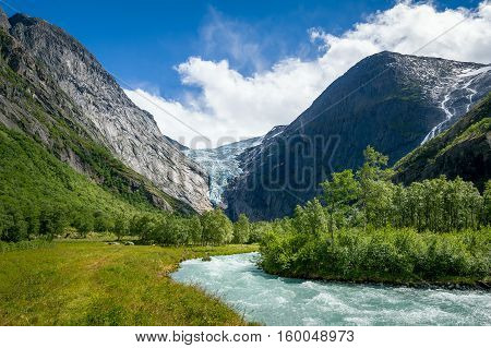Mountain river from melted ice on the hiking path to Briksdalsbreen Glacier. Norway national travel routes.