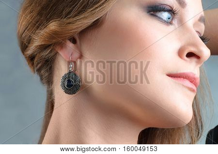 Beautiful model brunette with long hair and jewelry earrings