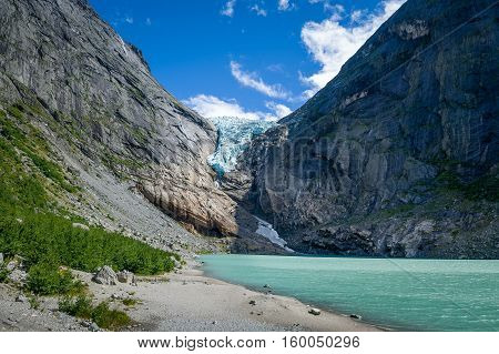 Briksdalsbreen glacier and lake with melted ice water. Popular Norway travel destination .