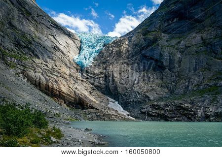 Briksdalsbreen glacier view, lightened by sun beam. Popular touristic hiking destination. Briksdal, Norway.