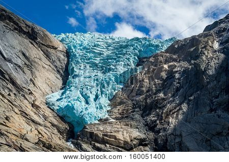 Close view of Briksdalsbreen glacier, turquoise ancient ice in the rocky mountains. Briksdal, Norway.