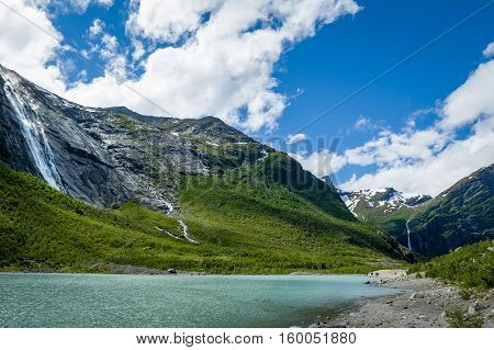 Melted ice lake landscape. Popular hiking path to Briksdalsbreen glacier. Norway.