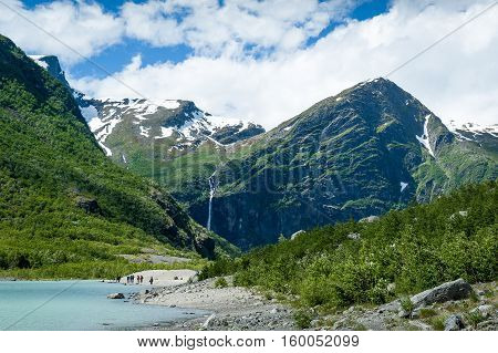Melted ice lake landscape and group of tourists. Popular hiking path to Briksdalsbreen glacier. Norway.