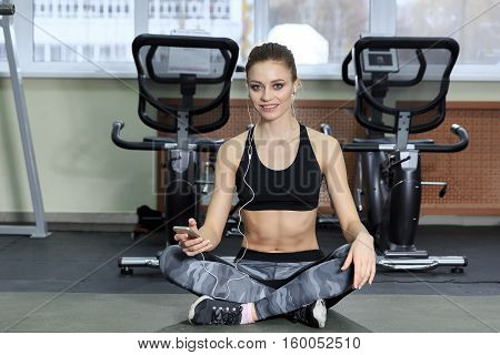 beautiful fitness girl sitting on the floor and listening to music in the gym.