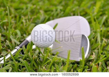Golf irons and ball on a tee laying on the fairway grass
