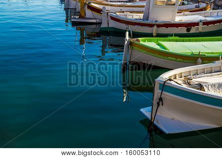 Mediterranean style owing boats in a glassy harbour