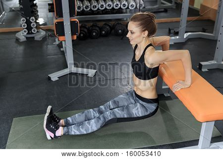 Beautiful slim brunette doing some push ups at the gym