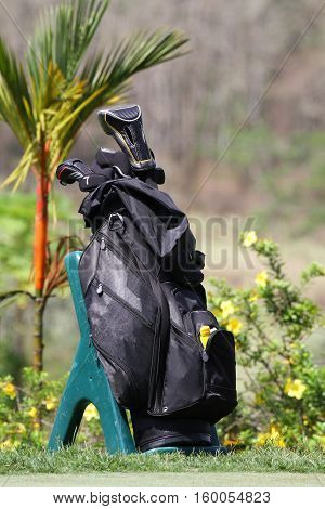 Black golf bag with clubs on a practice green at a golf course