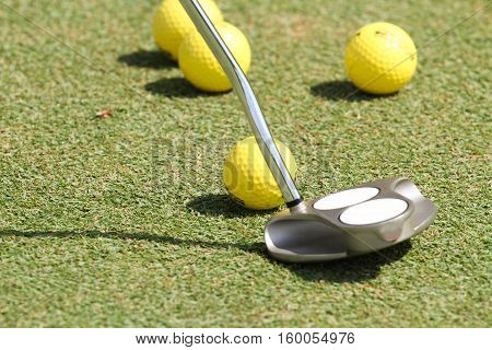 Practice golf balls and a putter on a green