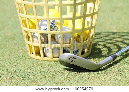 Macro shot of practice golf ball in a bucket and a golf iron on the green