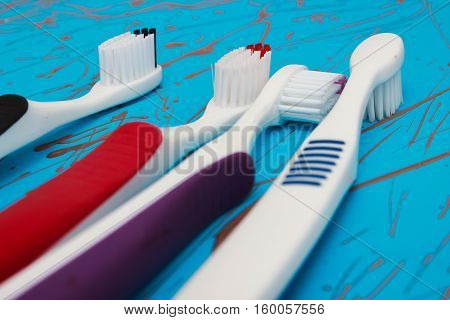Manual toothbrush set isolated on blue background. Four colours.