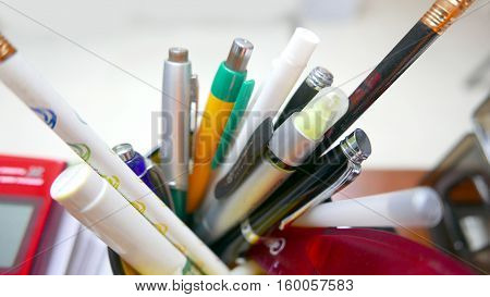 Macro shot of a container full of pens and pencils on an office desk