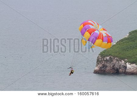 Close up of two persons on a Parasailing boat ride over the ocean going over an island
