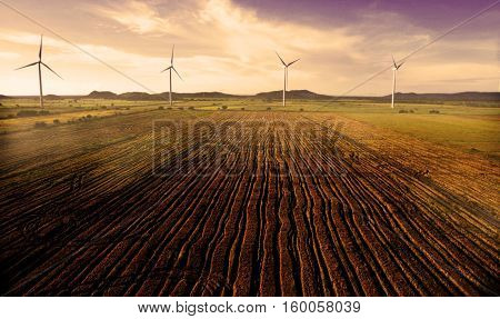 Harvested rice field near a wind turbine farm in the early morning light and fog