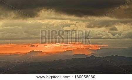 Beautiful warm sunrise with sun beams shining down over the mountains