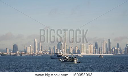Luxury boats anchored at sea with the impressive skyline of Panama City in the background