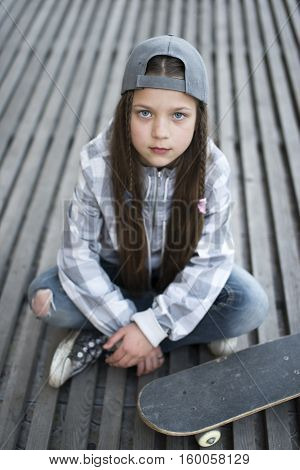 serious child girl with skateboard sitting on wooden deck