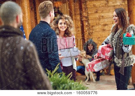 Smiling girls and guys preparing for Christmas celebration at mountain